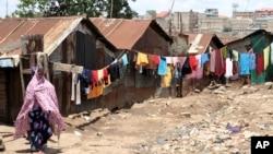 FILE - A woman walks on a street in the Korogocho slums in Kenya's capital Nairobi, April 6, 2011.