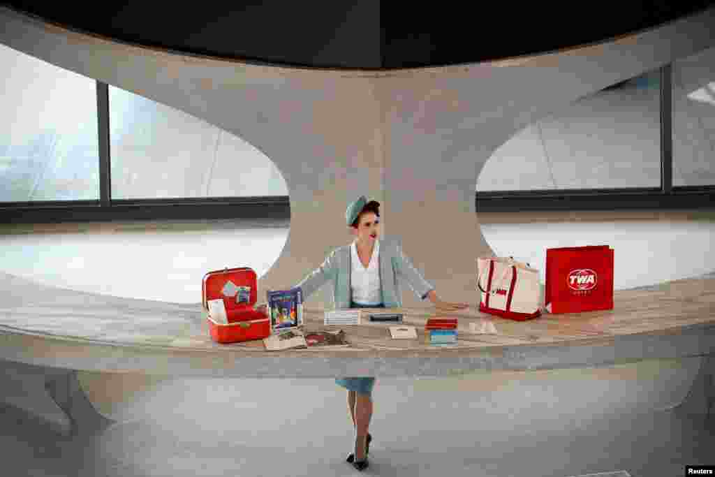 A worker stands behind a reception desk in the main lobby of the TWA Hotel, which is housed inside the former 1962 TWA Flight Center terminal which was designed by architect Eero Saarinen at JFK International Airport in New York, Oct. 2, 2019.
