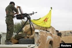 FILE - A YPG Kurdish fighter is seen atop a pickup truck near the city of Ras al-Ain, Syria, November 5, 2013.