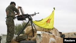 FILE - A Kurdish fighter is seen atop a pickup truck near the city of Ras al-Ain, Syria, Nov. 5, 2013.