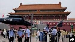 警察在北京天安門廣場為執勤崗位架設遮陽傘。(2021年6月23日)