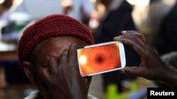 Seorang perempuan menjalani pemeriksaan mata menggunakan ponsel pintar di sebuah klinik di Mau Summit, sebelah barat Nairobi, Kenya. (Foto: Dok)