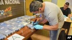 Un policier ouvre un paquet de cocaïne trouvé dans une annexe de l'ambassade de Russie à Buenos Aires, en Argentine, le 14 décembre 2016.