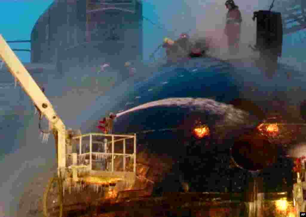 Another video image from Ru-RTR Russian state television channel shows firefighters work on the hull of the Yekaterinburg nuclear submarine. (AP Photo)