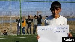 """Pengungsi Suriah Mustafa Halebi, (16 tahun) yang tinggal di kamp Nizip, Gaziantep, Turki membawa pamflet bertuliskan: """"Saya orang Suriah dan Ingin Kembali ke Suriah."""" (foto: ilustrasi)"""