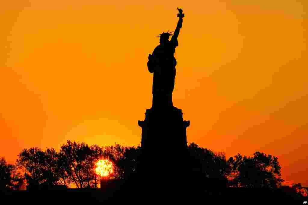 نمایی از پشت مجسمه آزادی در شهر نیویورک در آستانه طلوع آفتاب.