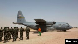 FILE - A C-130 U.S. Air Force plane taxis as Nigerien soldiers stand in formation during a military exercise in Diffa, Niger, March 8, 2014.