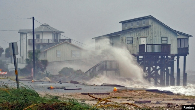 Waves crash on stilt houses along the shore as Hurricane Michael's power is unleashed in Alligator Point, Franklin County, Fla., Oct. 10, 2018.