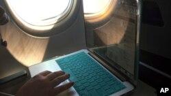 Seorang penumpang menggunakan laptopnya dalam penerbangan ke Atlanta dari Boston, 1 Juli 2017. (Foto: dok).