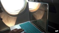 FILE - Seorang penumpang pesawat terbang menggunakan laptop dalam sebuah penerbangan maskapai komersil dari Boston ke Atlanta.