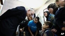 Tổng giám đốc UNICEF Anthony Lake (trái) nói chuyện với một bé trai đến một trung tâm y tế ở Damascus, Syria, để được uống vắc xin ngừa bại liệt, 29/10/13