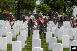 Soldados de la Vieja Guardia colocan banderas en las tumbas del Cementerio de Arlington, en Virginia, en anticipación al Memorial Day 2016.