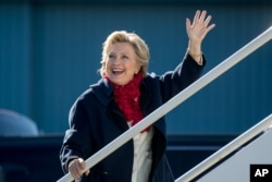 Democratic presidential candidate Hillary Clinton waves to members of the media as she boards her campaign plane at Westchester County Airport in White Plains, New York, Nov. 1, 2016, to travel to Florida for rallies.