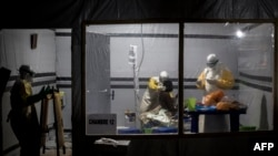 FILE - Health workers treat an unconfirmed Ebola patient inside a MSF (Doctors Without Borders)-supported Ebola Treatment Center (ETC) in Butembo, Democratic Republic of Congo, Nov. 3, 2018.