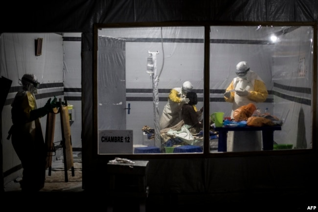 FILE - Health workers treat an unconfirmed Ebola patient inside an Ebola Treatment Center (ETC) in Butembo, Democratic Republic of the Congo, Nov. 3, 2018.