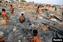 ພວກເດັກນ້ອຍຜູ້ຊາຍ ຊອກຫາສິ່ງຂອງທີ່ມີປະໂຫຍດ ໃນຂີ້ເຖົ່າ ຂອງພວກເຮືອນຊານທັງຫຼາຍ ຫຼັງຈາກຖືກໄຟໄໝ້ເຜົາຜານ ຢູ່ທີ່ສູນທີ່ພັກອາໄສຂອງພວກຊາວໂຣຮິງຢາ ມຸສລິມ ທີ່ຖືກພັດພາກຈາກຖິ່ນຖານໃນພາກຕາເວັນຕົກຂອງລັດ Rakhine ໃກ້ກັບເມືອງ Sittwe, ຂອງມຽນມາ, ວັນທີ 3 ພຶດສະພາ 2016.