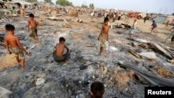 2016年5月3日,在缅甸西部实兑附近的诺开邦,大火摧毁了流离失所的罗欣亚穆斯林的临时住所,一群男童正在烧毁的住房废墟中寻找有用物品。