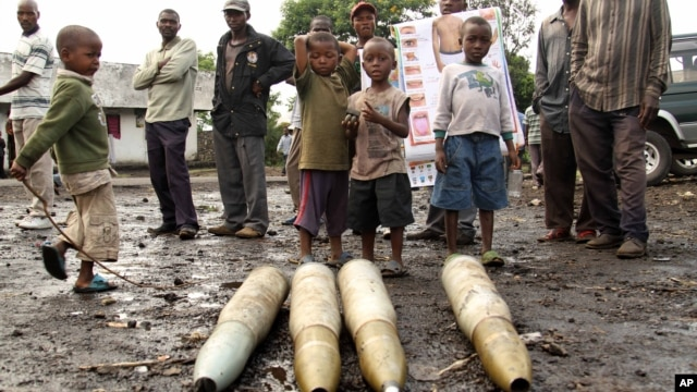 Congolese citizens look at tank shells lying next to roadside, left behind by retreating government troops as they fled assault by M23 rebels, in eastern Congo, Nov. 21, 2012.