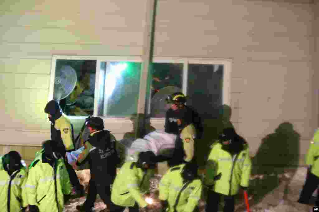 Rescue workers carry a body from a collapsed building in Gyeongju, South Korea, Feb. 17, 2014.