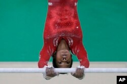 United States' Gabrielle Douglas trains on the uneven bars ahead of the 2016 Summer Olympics in Rio de Janeiro, Brazil, Aug. 4, 2016.