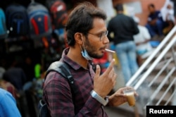 Seorang pria yang memakai masker pelindung wajah merokok di tengah penyebaran COVID-19 di kawasan tua Delhi, India, 20 Oktober 2020. (Foto: REUTERS/Adnan Abidi)