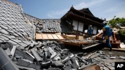 Equipos de rescate buscan personas atrapadas entre casas destruidas por el terremoto en Kumamoto, sur de Japón, el viernes, 15 de abril de 2016.