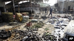 Residents and Iraqi soldiers inspect the site of a bomb attack in Khalis, northeast of Baghdad, December 1, 2011