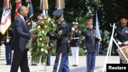 A member of an honor guard helps U.S. President Barack Obama (L) lay a wreath in honor of Memorial Day at the Tomb of the Unknowns in Arlington National Cemetery in Arlington, Virginia, May 28, 2012