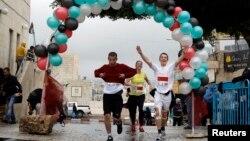 Para peserta lomba lari maraton internasional pertama di Palestina mencapai garis finis di kota Betlehem, Tepi Barat, Minggu (21/4).