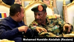Sudan's Head of Transitional Military Council, Lieutenant General Abdel Fattah Al-Burhan, talks to Ethiopia's Prime Minister Abiy Ahmed during the signing of the power sharing deal, that paves the way for a transitional government, and eventual elections,