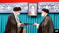 Supreme Leader Ayatollah Ali Khamenei, left, gives his official seal of approval to newly elected President Ebrahim Raisi, in Tehran, Iran, Aug. 3, 2021, in this photo released by an official website of the office of the Iranian supreme leader.