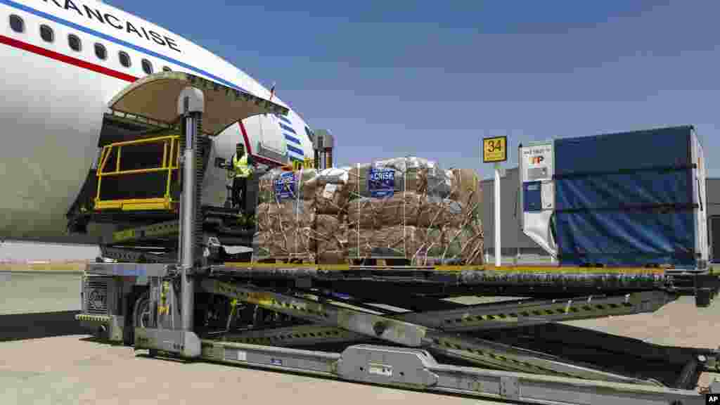 In this photo provided Aug. 11 by the French Army, airport employees unload humanitarian freight from a French Air Force plane at Irbil airport in Iraqi Kurdistan, Aug. 10. 2014.