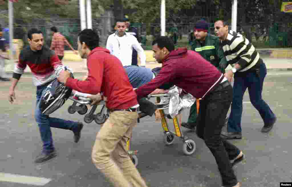 People use a stretcher to transport the body of a police officer who was killed in explosions near Cairo University, April 2, 2014.