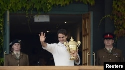 Roger Federer of Switzerland holds the winners trophy on the clubhouse balcony after defeating Andy Murray of Britain in their men's singles final tennis match at the Wimbledon Tennis Championships in London, July 8, 2012.