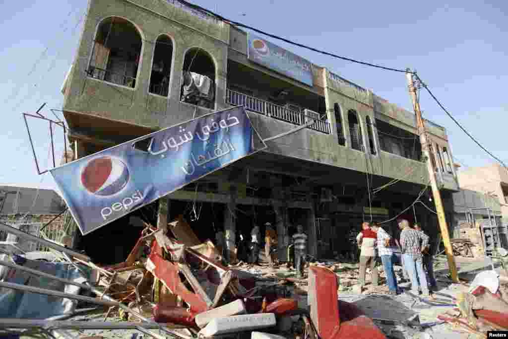 Residents gather at the premises of a coffee shop that was destroyed in a suicide bomb attack the night before, in Baghdad, June 17, 2013.