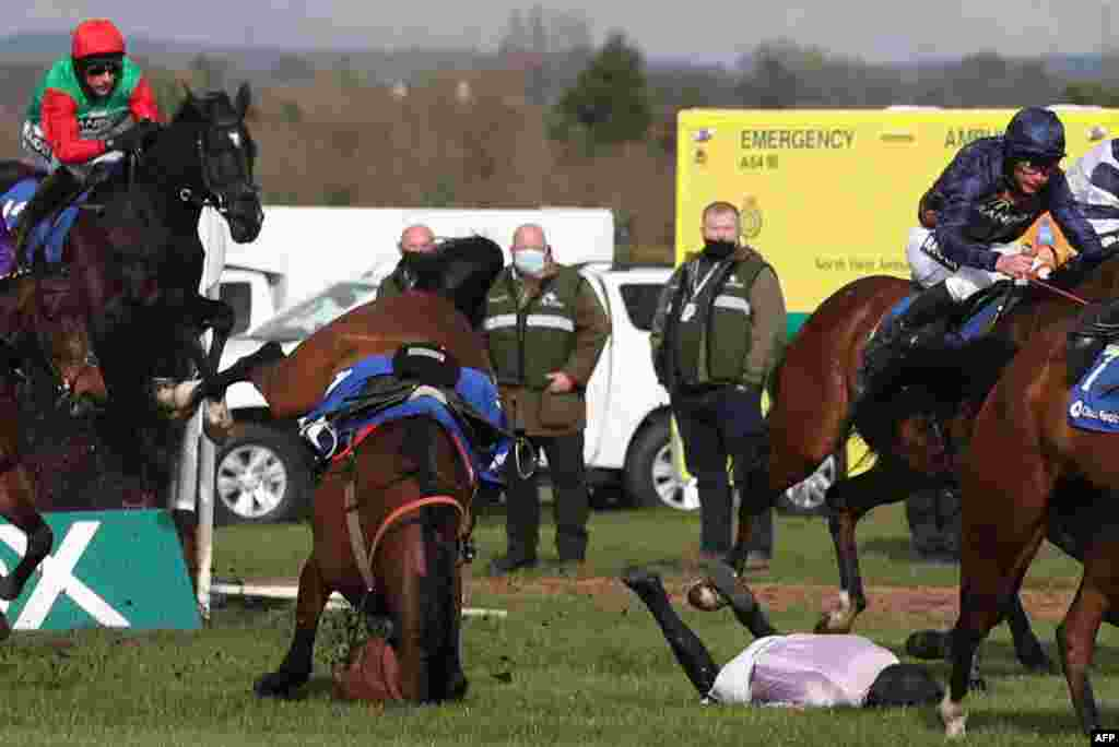 Getaway Trump and Harry Cobden fall during the Close Brothers Red Rum Handicap Chase on the first day of the Grand National Festival at Aintree Racecourse in Liverpool, north west England.