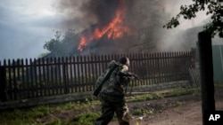 A pro-Russian armed man runs past a burning house after it was set on fire by a mortar shell, on the outskirts of the town of Lysychansk, Ukraine, May 22, 2014.