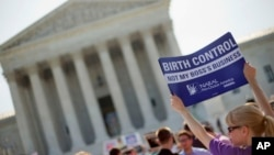 FILE - Demonstrator holding up a sign outside the Supreme Court in Washington, June 30, 2014. The Obama administration announced new measures Aug.22 to allow religious non-profits and some companies to opt out of paying for birth control for female employees whi