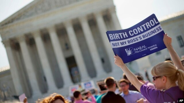 Demonstrator holding up a sign outside the Supreme Court in Washington, June 30, 2014. The Obama administration announced new measures Aug.22 to allow religious non-profits and some companies to opt out of paying for birth control for female employees whi