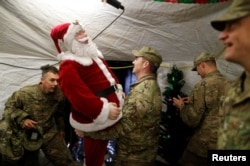 U.S. soldiers enjoy a Christmas dinner at an army base in Karamless town, east of Mosul, December 25, 2016. REUTERS/Ammar Awad