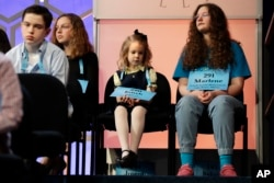 Edith Fuller, 6, of Tulsa, Okla., center, the youngest speller ever in the National Bee, sits next to Marlene Schaff, 14, of Lake Forest, Ill., right, as they wait to compete in the 90th Scripps National Spelling Bee in Oxon Hill, Md., May 31, 2017.