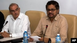 FILE - Humberto de La Calle, left, head of Colombia's government peace negotiation team, listens as Ivan Marquez, chief negotiator of the Revolutionary Armed Forces of Colombia reads a joint statement in Havana, Cuba, Oct. 28, 2016.