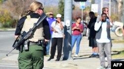 Una oficial de policía fuertemente armada establece el perímetro alrededor del sitio del tiroteo en San Bernardino, California.