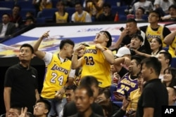 Chinese fans react during a preseason NBA basketball game between the Brooklyn Nets and Los Angeles Lakers at the Mercedes Benz Arena in Shanghai, China, Oct. 10, 2019.