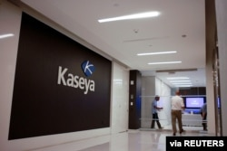 FILE - Staff enter the headquarters of information technology firm Kaseya in Miami, in an undated still image from video.