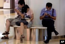 중국 베이징의 쇼핑센터에서 시민들이 스마트폰을 사용하고 있다.