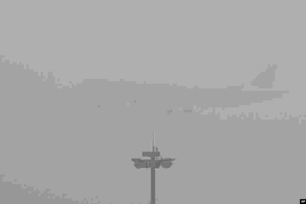 Sebuat pesawat penumpang maskapai Air China siap mendarat di bandara internasional Beijing yang diselimuti kabut polusi tebal.