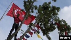 FILE - A supporter of Turkey's main pro-Kurdish Peoples' Democratic Party (HDP) stands in a tree during a campaign event in Istanbul, Turkey, May 25, 2018.