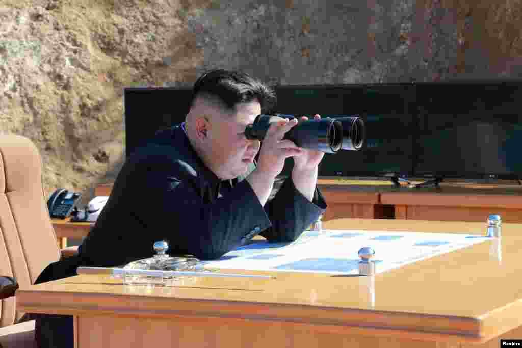 김정은 북한 국무위원장 대륙간탄도미사일 '화성-14형' 시험발사 장면을 쌍안경으로 지켜보고 있다.