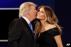FILE - Republican presidential nominee Donald Trump kisses wife Melania Trump after the presidential debate at Hofstra University in Hempstead, N.Y., Sept. 26, 2016.
